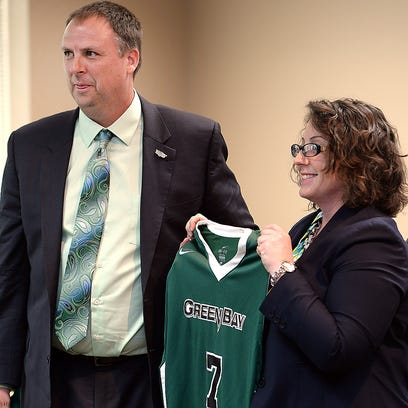 UW-Green Bay athletic director Mary Ellen Gillespie holds a jersey as she introduces new men's basketball coach Linc Darner at the Kress Events Center.