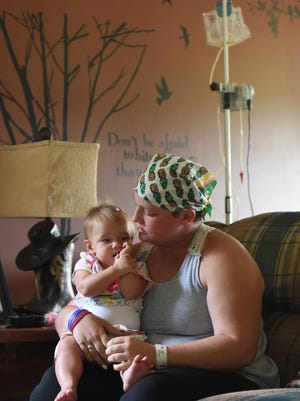 Hope Smith sits with her daughter Corinn, 11 months, in their Chandlersville home. Smith, 18, has stage three nasopharyngeal carcinoma, and is looking forward to returning to school and a career in law enforcement. A fundraising benefit for Hope will be held from noon to 3 p.m. Saturday, at Zane's Landing Park.