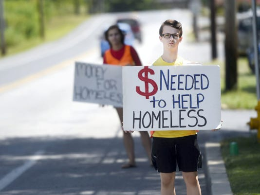"Josh Marshall, 13, and Abby Weisman, 14, hold signs seeking donations for the Lebanon Homeless Shelter on Saturday. The Rescue Hose Co. Social Club hosted its Seventh Annual ""Hobos in the Outfield"" event to build awareness of and raise money to fight homelessness. The group had hoped to raise 2,000."