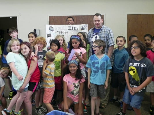 Instructor Jim Boyle is pictured with students who participated in the twice-a-week summer chess camp at Montessori Academy.