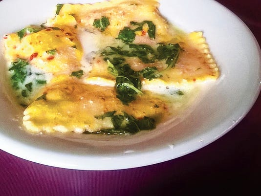 The half order of crab ravioli (13.50) is served in a lemon butter sauce with basil. All entrees come with complimentary bread and a choice of soup or salad.