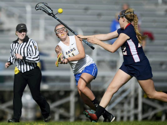 Kennard-Dale's Emmie Dressel passes under pressure from New Oxford's Gracie Ernst during a girls' lacrosse game at Kennard-Dale High School on April 28. The Rams beat the Colonials, 24-11.