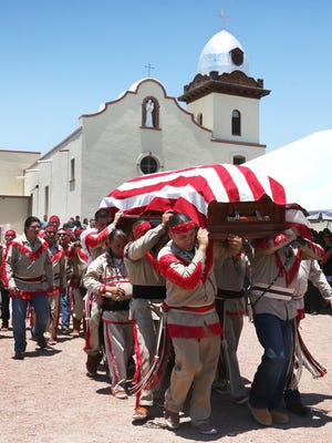 "Ysleta del Sur Pueblo members carry the flag-draped coffin of Francisco ""Frank"" Holguin, the T' aikabede, or chief, of the Tiguas, out of Our Lady of Mount Carmel Mission at 131 S. Zaragoza Road on Wednesday. Holguin, 96, died Friday."