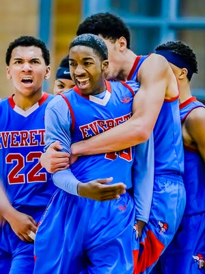 Devon Hudson ,center, of Everett is congratulated by his teammates after knocking down a 3-point shot to put Everett up 48-40 with 2:36 remaining in the 4th quarter of the Vikings' Class A district final game with Grand Ledge Friday March 13, 2015 at Okemos High in Okemos. KEVIN W. FOWLER PHOTO
