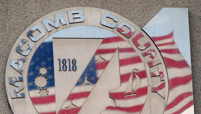 The United States flag is reflected in the Macomb County seal on the Administration Building.