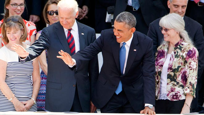Vice President Joe Biden, left, and President Barack Obama wave to members of the Tragedy Assistance Program for Survivors (TAPS), for people who have a family members who died in the military, after Obama spoke during a Memorial Day Observance at Arlington National Cemetery in Arlington, Va., Monday, May 26.