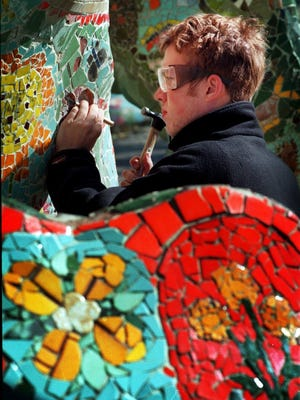 Travis Nicholson uses a hammer and chisel to remove some bad tiles from the dragon sculpture at Fannie Mae Dees Park on Nov. 11, 1998.