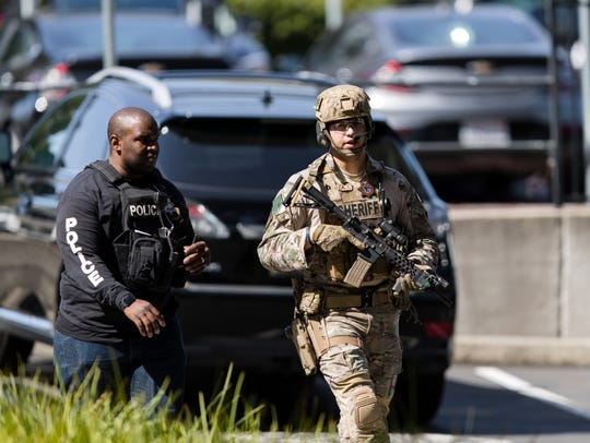 Law enforcement personnel stand watch outside of the