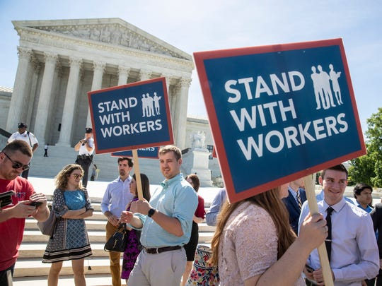 People gather at the Supreme Court, Monday, June 25, 2018, awaiting a decision in an Illinois union dues case, Janus vs. AFSCME, in Washington.  The Supreme Court says government workers can't be forced to contribute to labor unions that represent them in collective bargaining, dealing a serious financial blow to organized labor.