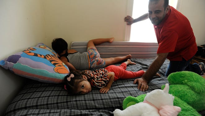 Hossam Alrostem with his son Wisam, 7, and daughter Maisa, 3, as they lay in their bed in the family's Jersey City apartment. Alrostem spoke of his family's escape from their home in Syria to a refugee camp in Jordan before being granted asylum and arriving in the United States on June 16. DANIELLE PARHIZKARAN/STAFF PHOTOGRAPHER.