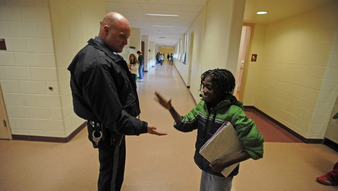 Totowa Police Officer Pontenzone, greets student Schneider Altenor, age 11, at the Washington Park School, on Thursday, Jan. 3, 2013. Totowa has decided to hire borough cops to stand guard each day in the districts two schools, in reaction to the Sandy Hook Elementary school in Newtown, CT., in December.
