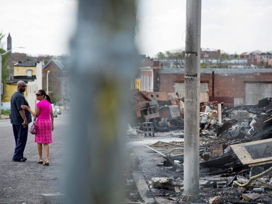 The remains of a senior center under construction that burned during the riots following Freddie Gray's funeral stands at right as churchgoers walk by following a service at Southern Baptist Church on Sunday in Baltimore.