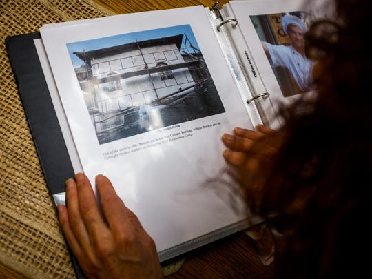 MariaElena (Ellen) Chavez looks at a document she made containing photos, captions and stories detailing her recent public service trip to Albania.