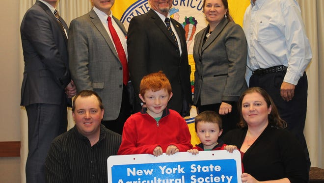 The New York State Agricultural Society Forum  honors Whittaker Farms of Whitney Point for 100 years of continuous operation on Jan. 7. Pictured in the front row are, from left, Brock, Andrew, Brandon and Ashley Whittaker. Pictured in the back row are, from left, Tom Cosgrove of Farm Credit NE AgEnhancement; Hans Kunze, president of the NYS Agricultural Society; Richard Ball, commissioner of the New York Department of Agriculture and Markets; and Judy and Scott Whittaker.