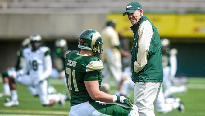 CSU football coach Mike Bobo talks to tackle Sam Carlson before the start of last year's spring football game. The Rams will start spring practices March 25  and play this year's spring game April 23 at Hughes Stadium.