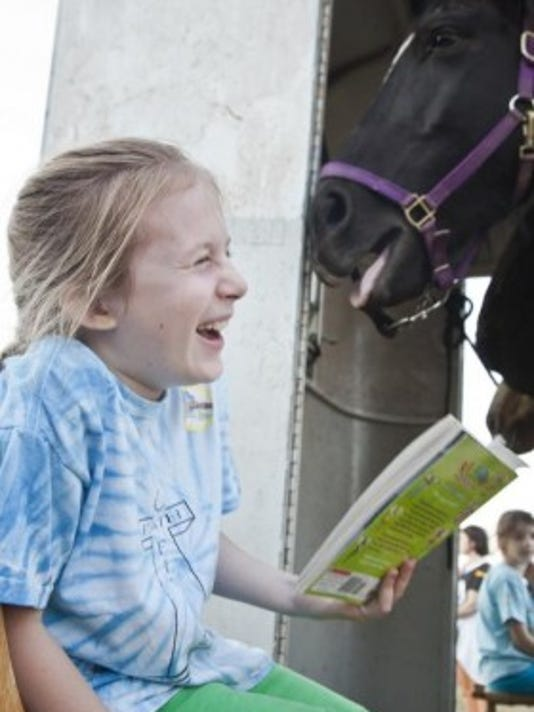 Patriot the horse accidentally sneezes on Mackenzie Wagaman, 10, as she reads to him at Collinsville Community Library recently. Yep, this is part of what your library might offer. (YORK DAILY RECORD/SUNDAY NEWS -- SONYA PACLOB)