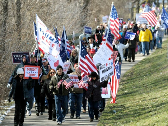 Trump supporters march east on the bike path along Metro Parkway in Clinton Township, Mich., Saturday, March 4, 2017.