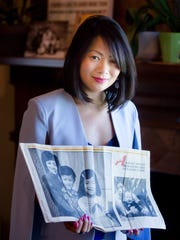 Nu Huynh holds a copy of a 1983 Des Moines Register