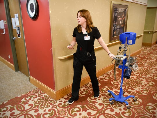 Maggy Hiza, house charge supervisor, moves equipment to a room Tuesday, March 7, at CentraCare Health's St. Benedict's Senior Community.