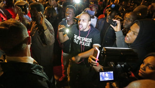 Crowds confront police near the scene in south St. Louis where a man was fatally shot by an off-duty St. Louis police officer on Wednesday, Oct. 8, 2014.