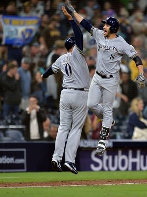 The Brewers' Ryan Braun is congratulated by third base coach Ed Sedar after hitting a three-run homer in the ninth innings.