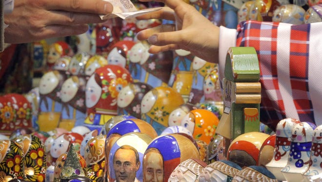 Matryoshkas, traditional Russian nesting dolls, depicting Russian President Vladimir Putin are displayed for sale at a shop near the Red Square in Moscow, Russia on Dec. 15, 2014. The Russian ruble dropped to an all-time low against the dollar at 58.35 and the euro at 72.66.