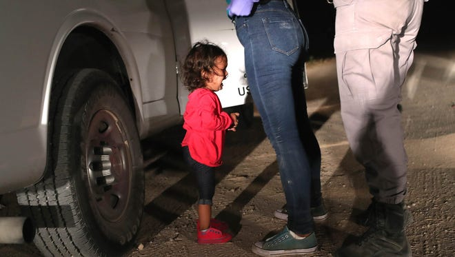 A 2-year-old Honduran asylum seeker cries as her mother is searched and detained near the U.S.-Mexico border on June 12, 2018 in McAllen, Texas. The asylum seekers had rafted across the Rio Grande from Mexico and were detained by U.S. Border Patrol agents before being sent to a processing center for possible separation.