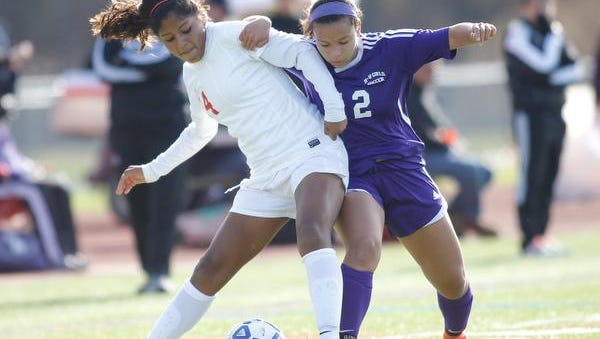 North Rockland's Maria Cabrera, left, works to gain possession against Monroe-Woodbury's Hannah Geller during the first half of the Class AA regional final at Arlington High School on Sunday.