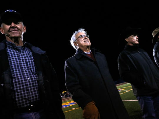 Lyle Guffey, left, Terrence Archunde, Grady Hampton and other members of the 1966 Bloomfield High School football team are honored during a halftime ceremony on Friday at Bobcat Stadium in Bloomfield.