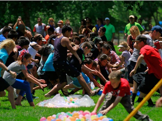 Participants race for water balloons on July 4, 2016, during a water balloon fight during Freedom Days' Party in the Park at Brookside Park in Farmington.