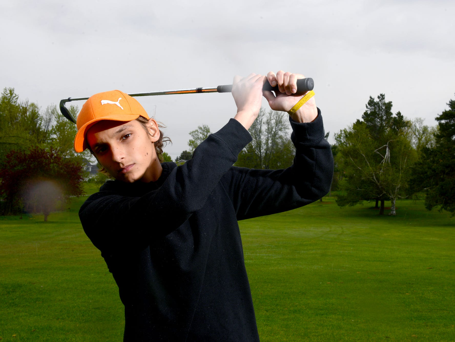"""Cayden Patrick continues to battle nasopharyngeal carcinoma, a rare form of cancer, however he still an active member of the Laingsburg High School golf team. He's pictured here, with """"Cayden's Team"""" bracelet, Tuesday, May 10, 2016 at the Pine Hills Golf Course in Laingsburg."""