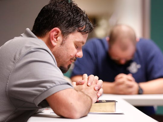 Adam Winn joins men in prayer after reading portions