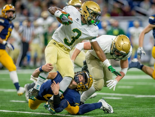 Ithaca's Joey Bentley, bottom, tackles Lumen Christi's
