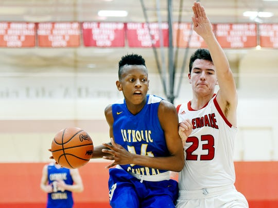 At left, Catholic Central's Mykel Bingham, brother and teammate of MSU commit Marcus Bingham Jr., drives to the basket as Allendale's Nathan Jenks defends during Central's game against Allendale on Tuesday, Jan. 16, 2018, at Allendale High School.