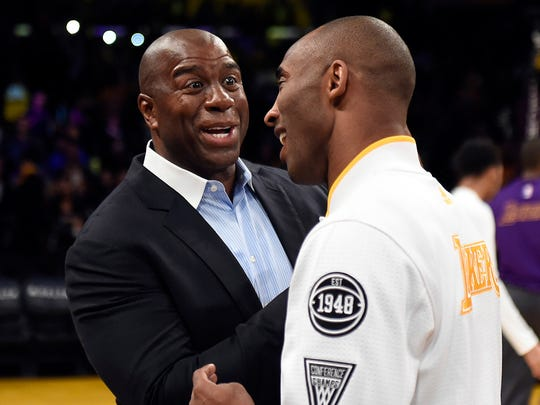 Kobe Bryant and Magic Johnson talk before a game against the Charlotte Hornets at Staples Center.