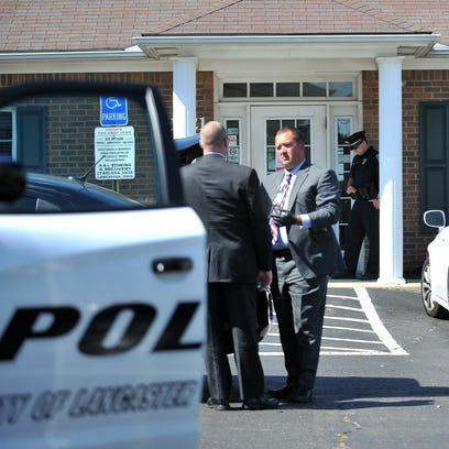 Lancaster Police detectives talk in the parking lot