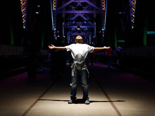 I came across Celiq Maddox, age 8, while working on a story on the Big Four Bridge and the spiritual affect it has on many that travel across it.  I had just moved with my camera to the center of the bridge to take advantage of the hanging light, when Celiq spotted me, raised his arms and looked skyward.  A perfect photo to lead the story. Sept. 18, 2015.