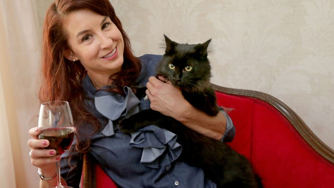 Katy McHugh, of Whitefish Bay, holds her rescue cat, Sebastian at her home. McHugh is looking to open Milwaukee's first cat cafe, Sip & Purr, featuring wine, snacks, coffee and adoptable cats. She's looking for a location for the cafe, which is scheduled to open in 2018. McHugh has already locked in a partnership with Lakeland Animal Shelter, which will provide the adoptable cats.