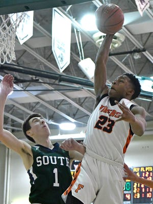 Fern Creek's Tony Rogers (23) goes in for a dunk past the defense of South Oldham's Devin Young (1) during the second half of the Mitchell Irvin Tournament, Thursday, Dec. 29, 2016 in Crestwood KY.