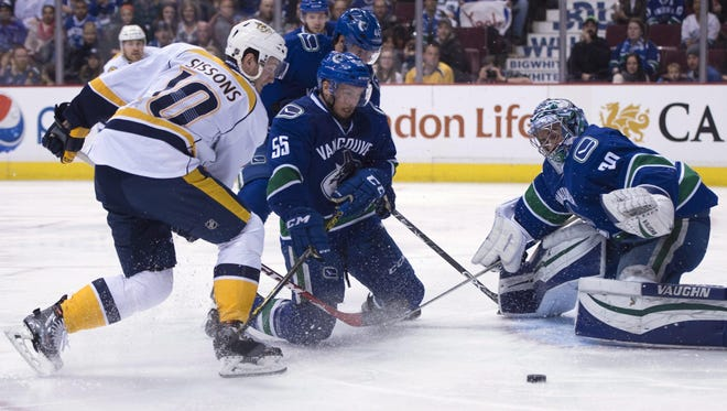 Canucks defenseman Alex Biega (55) tries to stop a shot from Predators center Colton Sissons (10) as Canucks goalie Ryan Miller (30) watches in the first period Saturday.