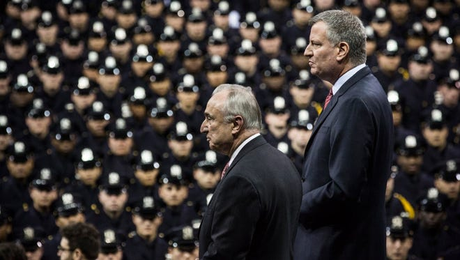 NYPD Commissioner William Bratton, left, and Mayor Bill de Blasio attend a NYPD graduation ceremony at Madison Square Garden on December 29.
