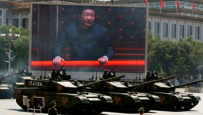 Chinese President Xi Jinping is displayed on a screen as tanks take part in a parade in Beijing in 2015.