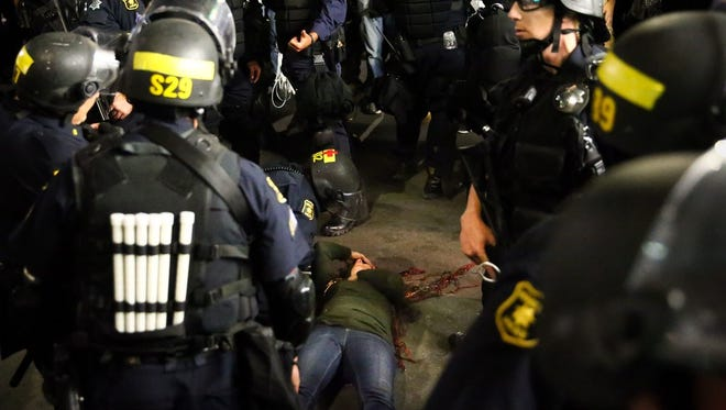 Police officers surround a fallen supporter of conservative commentator Ben Shapiro after she was knocked to the ground during a scuffle with protesters following a speech by Shapiro on Sept. 14 at the University of California, Berkeley.