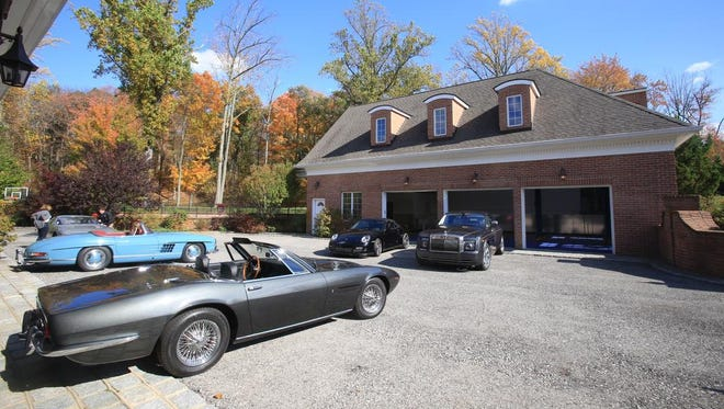 Luxury cars like 1965 Aston Martin convertible, Bentley, Mercedes and 1986 Porche 911 are parked in front of the two garages at a luxury home for sale at 23 Hollow Ridge Road in Bedford Corners on  Oct. 18, 2014.