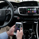 In this Thursday, Aug. 20, 2015 photo, Chris Martin from Honda North America demonstrates Apple CarPlay in Torrance, Calif. Playing deejay with voice commands will get easier for more Americans this fall as some best-selling cars get updated with software that integrates smartphones into the dashboard.