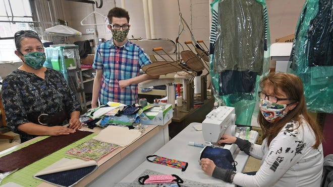 When they're not filling dry cleaning orders, employees of Young's Cleaners, 4001 W. Ridge Road in Millcreek Township, make face masks to slow the spread of COVID-19, the new coronavirus. Shown at the business in April are, from left: Elizabeth Solis, Stephen Beebe and Debbie Kacny.