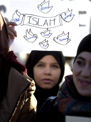A muslim woman holds a poster in Madrid on Sunday.