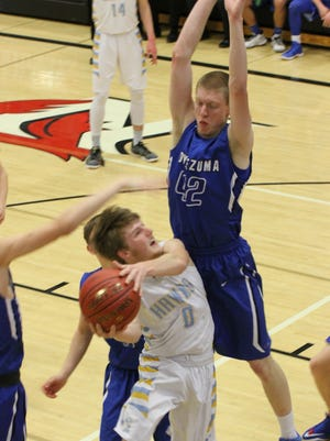 Vance Bushong, 42, Montezuma, aims to block Lynnville-Sully's Brevin Hansen, 0, during the Hawks' 58-45 win in the Class 1A District 10 finals.