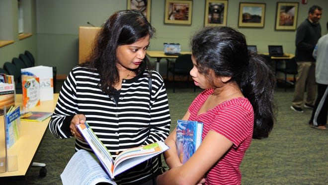 Sushma Pandrangi helps daughter, Nandini pick out books at the Northville Public Library as she prepares for the Northville Middle Schools, Science Olympiad held next year.
