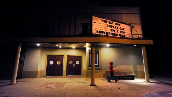 A teen walks past the M3 Palace Theater in Colorado City Saturday night, Jan. 28, 2017. The movie house installed a new digital projector two weeks ago after a long fundraising effort.